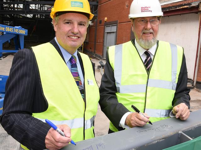 Paul Dickerson and the Chair of the Board of Governors, Geoff Dawson sign the steel.